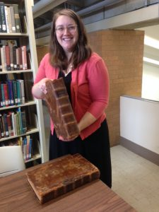 "Librarian Elizabeth Hartig with the ""new"" Bible for the rare books room."