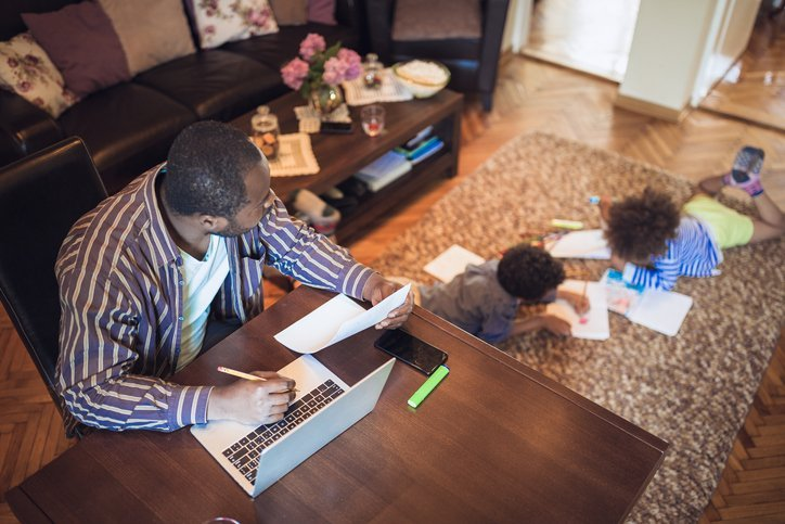 A middle-aged dad watches his kids as he works on a laptop